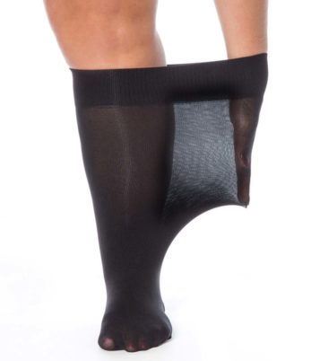 Woman's left leg. Plus size 40 denier black knee high. Woman's hand stretching band of knee high.